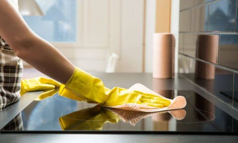 woman cleaning built-in induction cooktop