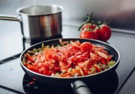 Frying pan with vegetables on induction cooker