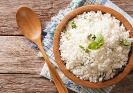 white rice in light brown wood bowl with spoon