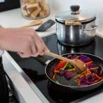 man cooking stir fry on induction cooktop