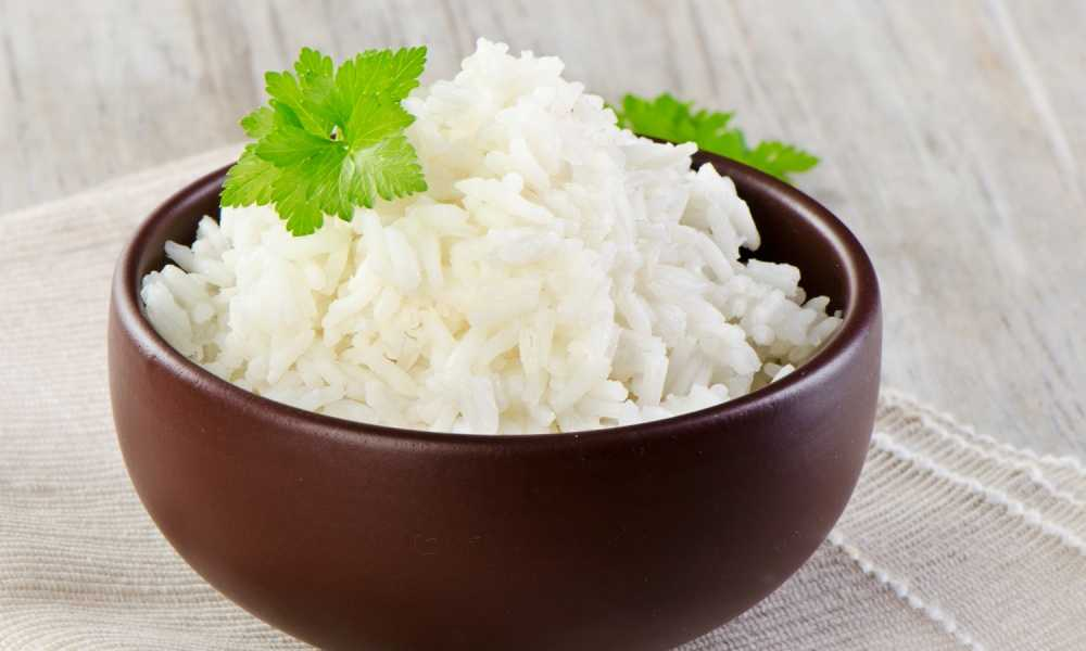 white rice with garnish in brown wood bowl