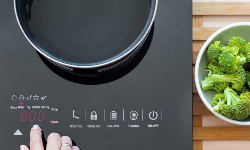 woman pressing button on portable induction cooktop