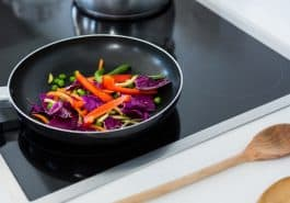 frying pan with vegetables on induction cooktop