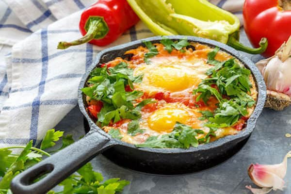 cast iron frying pan with eggs in tomato, onion, garlic, pepper and green parsley sauce.