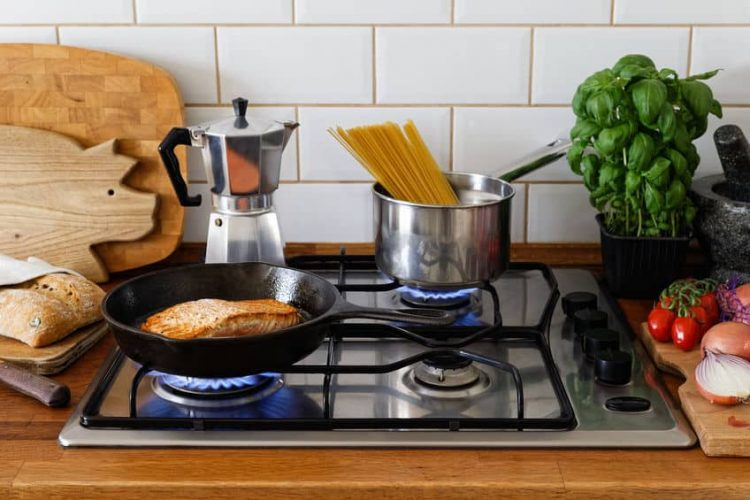 stainless steel pot and cast iron pan on built-in gas stove
