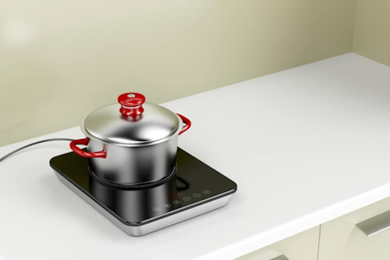 modern single burner induction hob with stainless steel pot and lid on surface