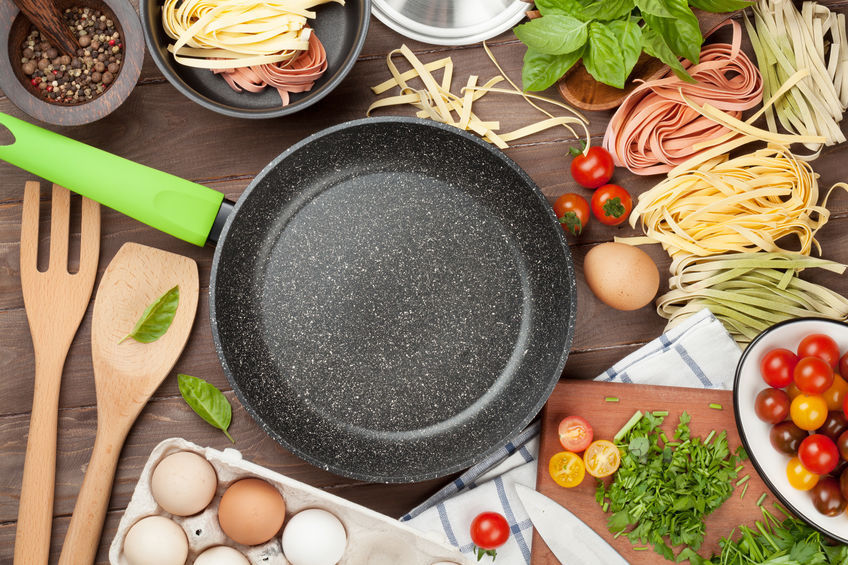 Frying pan with Pasta cooking ingredients and utensils on wooden table