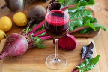 Red beet juice in a glass with fresh root