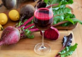 Red beet juice in a glass on a wooden table