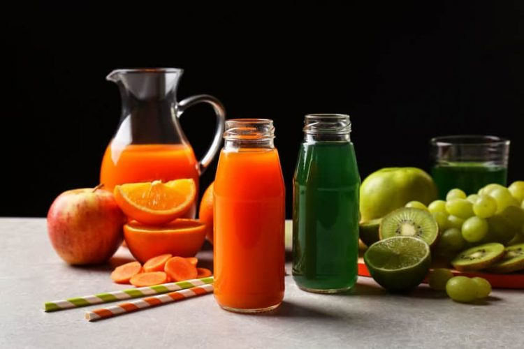 Delicious juices in bottles and fruits on table