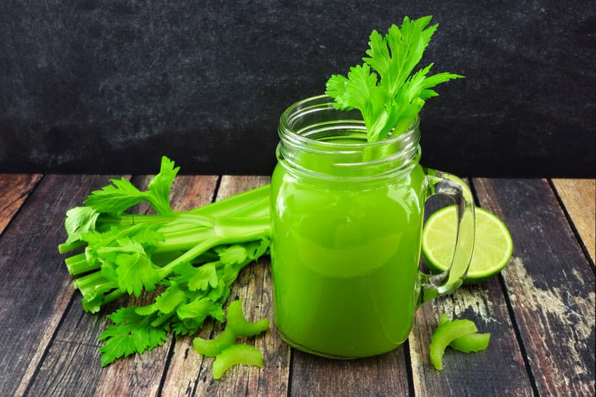 celery juice with fresh celery and lime on rustic wooden table
