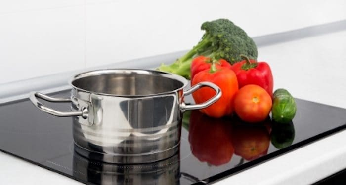 stainless steel pot and vegetables on induction stove