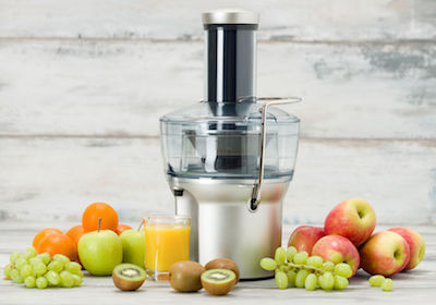 Electric juicer, various fruit and glass of freshly made juice