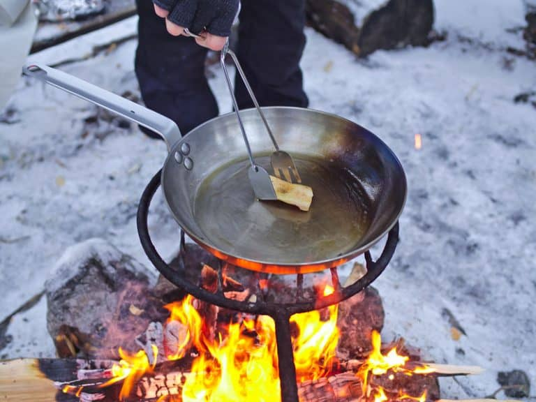 Seasoning carbon steel pan with lard on open camp fire.