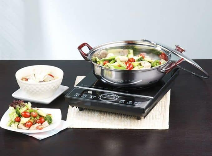 induction cooktop with pot of vegetables cooking