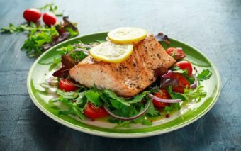 Baked salmon steak with tomato, onion, mix of green leaves salad on a plate.