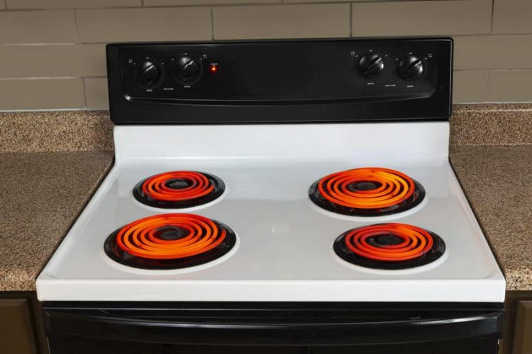 stovetop of an electric range with all the burners turned to high and glowing red.
