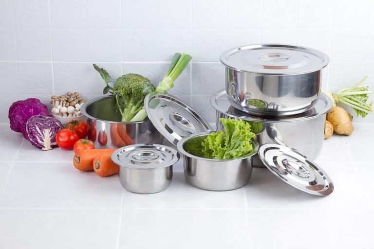 set of stainless pots with lids and vegetables