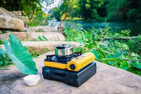 butane camping stove with aluminum teapot for boiling water