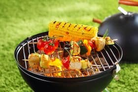 camping grill with corn on the cob and vegetables