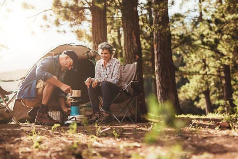 senior couple car camping in wilderness cooking with small stove