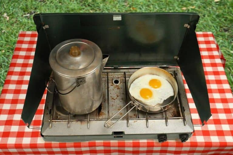 two burner camping stove, frying eggs, and coffee pot