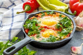 cast iron frying pan with eggs in tomato, onion, and parsley sauce
