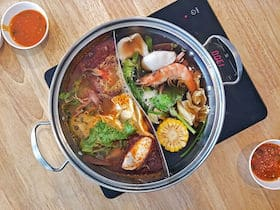 japanese hot pot shabu with double side pot with spicy and soya black soup separate on each side on induction stove