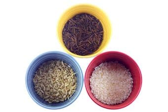 Various kinds of rice in colorful cups white on background