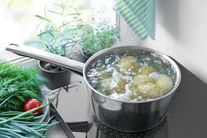 Boiling potato on induction cooker in kitchen