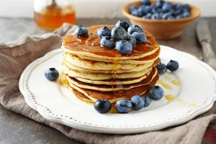 pancakes with blueberries and honey on plate