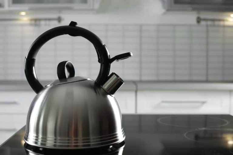 Modern kettle with whistle on stove in kitchen