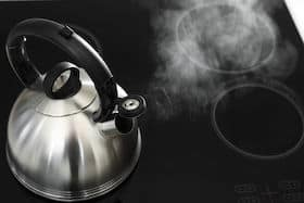 Modern kettle with whistle on stove