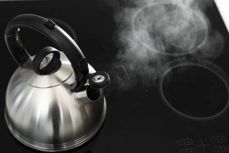 Modern kettle with whistle on stove, above